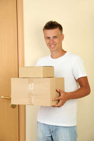 Young delivery man with parcels photo