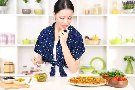 selects: Bella ragazza sceglie la pizza o la dieta su sfondo cucina