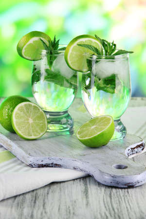 Glasses of cocktail with ice on board on napkin on wooden table on nature background photo