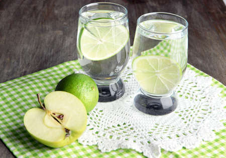 Glasses of cocktail with lime on napkin on dark wooden table photo
