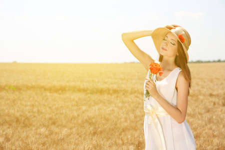 Portrait of beautiful young woman with poppies in the field photo