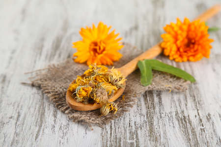 Fresh and dried calendula flowers on wooden background photo