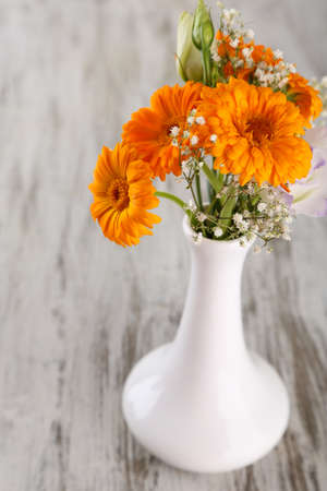 Calendula flowers in vase on wooden background photo