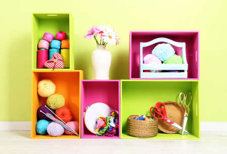 Colorful shelves of different colors with utensils on wall background photo