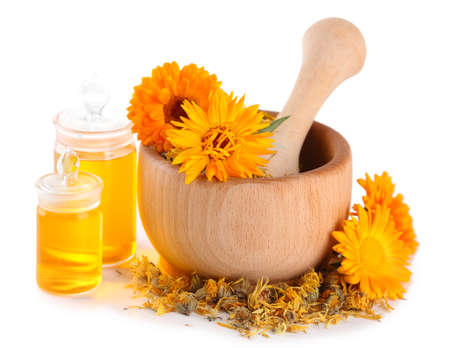 Medicine bottles and calendula flowers in wooden mortar isolated on white photo
