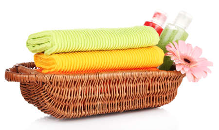Colorful towels and cosmetics bottles in basket, isolated on white photo