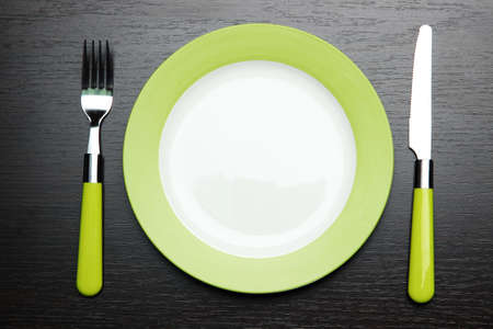 Knife, color plate and fork, on wooden background photo