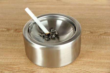 Metal ashtray and cigarette on wooden table photo
