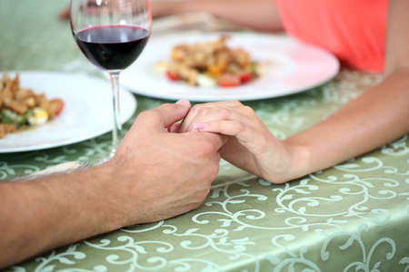 Hands of romantic couple over a restaurant table photo