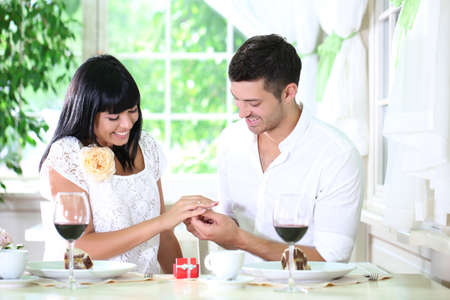 Man proposing and holding up an engagement ring his woman over restaurant table photo