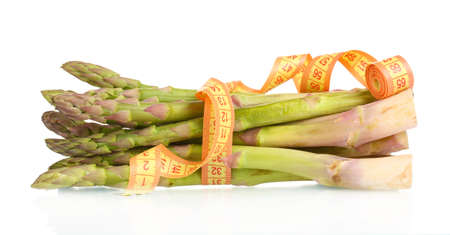 delicious asparagus and measuring tape isolated on white photo