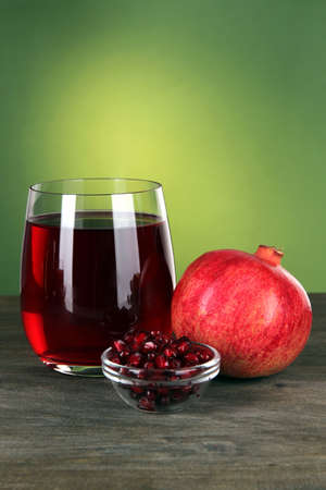 Glass of fresh garnet juice on table on green background photo