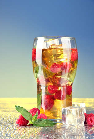 Iced tea with raspberries and mint on blue background photo