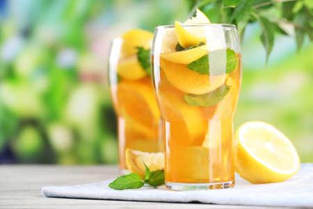tea garden: Iced tea with lemon and mint on wooden table, outdoors