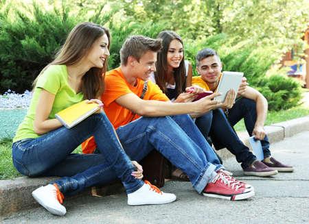 Gelukkige groep jonge studenten die in park zitten