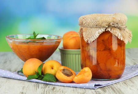 Apricot jam in glass jar and fresh apricots, on wooden table, on bright background photo
