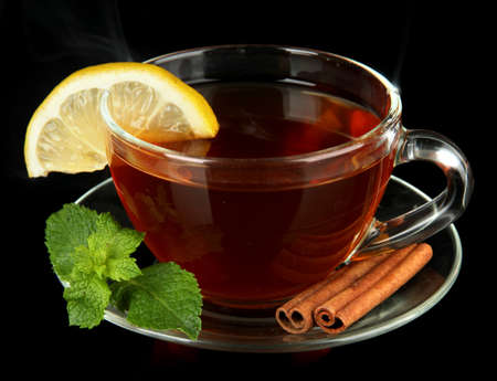 Cup of tea with lemon isolated on black photo