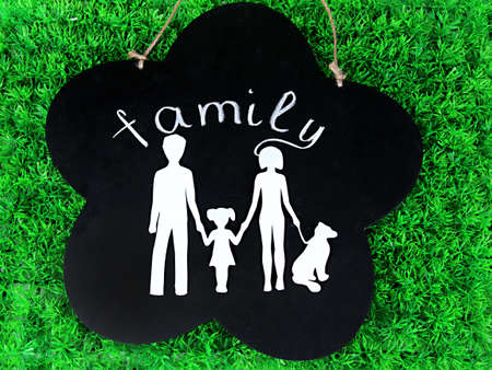 Family from paper on wooden board on bright background photo