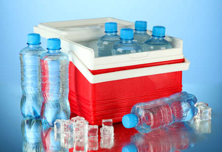 Traveling refrigerator with bottles of water and ice cubes, on blue background photo