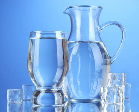 Glass pitcher of water and glass on blue background photo