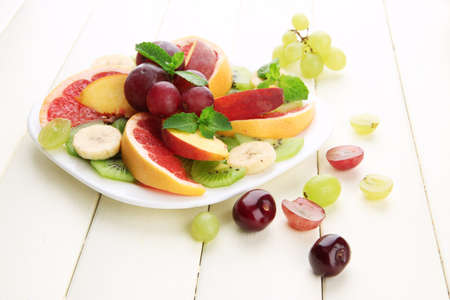 Assortment of sliced fruits on plate, on white wooden table photo