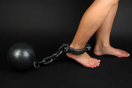 Legs in heavy iron shackles on dark background photo