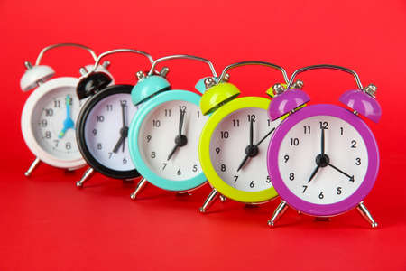 Colorful alarm clock on red background photo