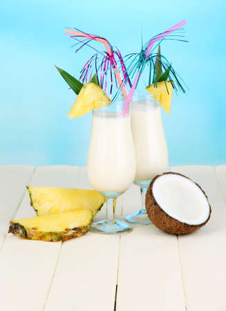 Pina colada drink in cocktail glasses, on bright background photo