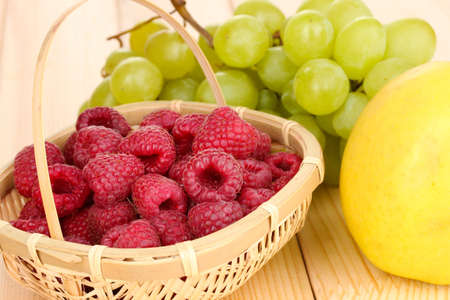 ripe sweet grapes and apple on wooden background photo