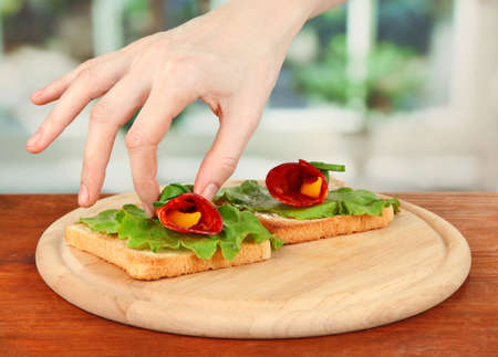 Process of preparing salami rolls on roasted bread ,on bright background: female hand puts  salami roll with piece of paprika on roasted bread Stock Photo - 21321083