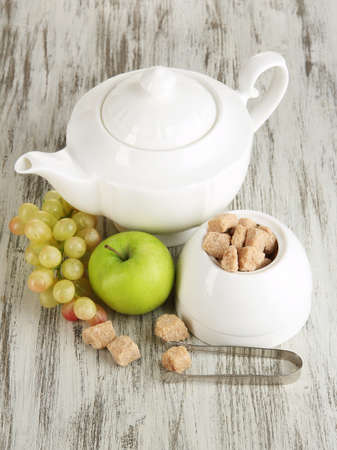 Unrefined sugar in white sugar bowl on wooden background photo