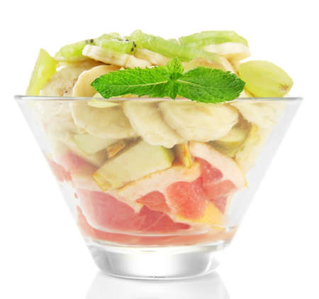 Tasty fruit salad in glass bowl, isolated on white photo