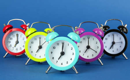 Colorful alarm clock on blue background photo