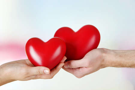 Hearts in hands on light background photo