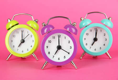 Colorful alarm clock on pink background photo