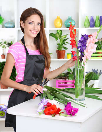 Beautiful girl florist with flowers in flowers shop Imagens