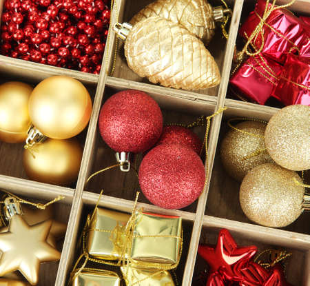 group of christmas baubles: Wooden box filled with christmas decorations, isolated on white