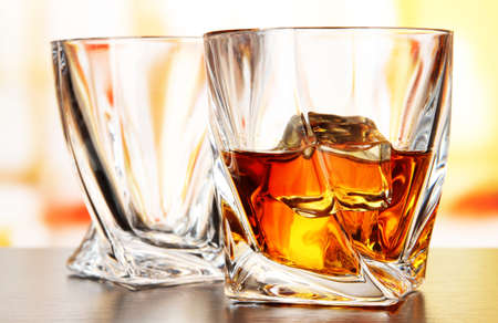 Glasses of whiskey, on bright background photo