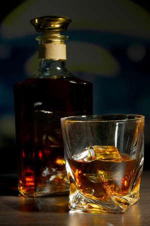 whiskey bottle: Glass of whiskey with bottle, on dark background