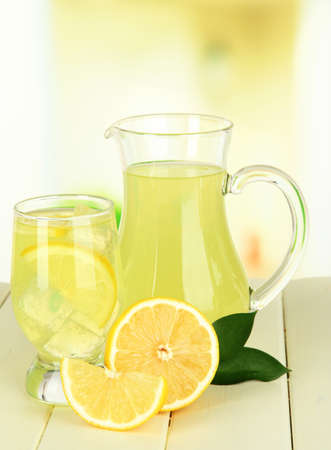 pitcher: Delicious lemonade on table on light background