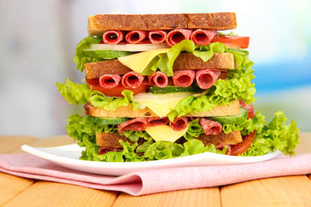 Huge sandwich on wooden table, on bright background photo