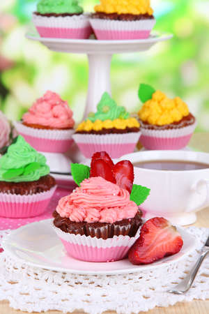 Beautiful cupcakes on dining table on natural background photo