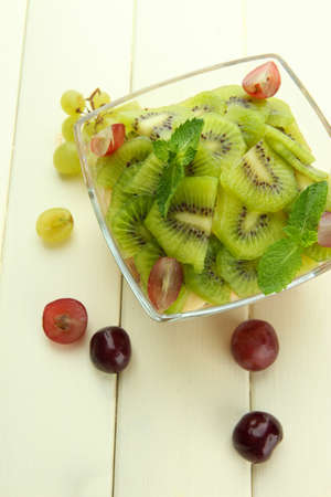 Tasty fruit salad in glass bowl, on white wooden table photo