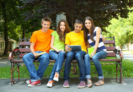 Happy group of young students sitting in park photo