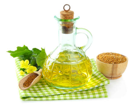 Jar of mustard oil and seeds with mustard flower on wooden background photo