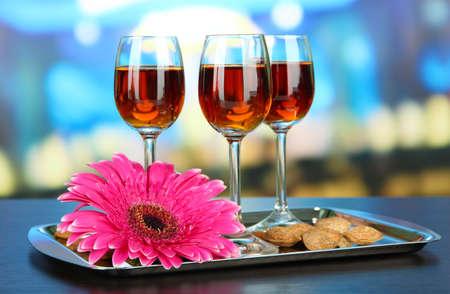amaretto: Glasses of amaretto liquor and roasted almonds, on tray, on bright background