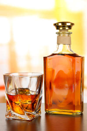 alcohol bottles: Glass of whiskey with bottle, on dark background