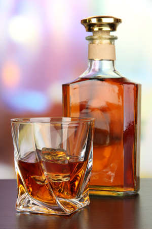 Glass of whiskey with bottle, on dark background photo