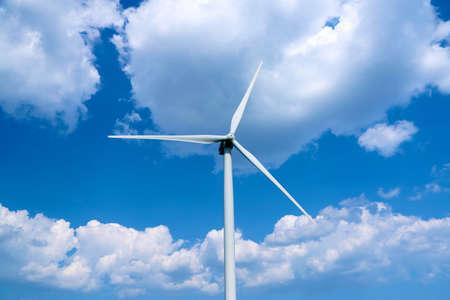 Windmill in field on blue sky background photo
