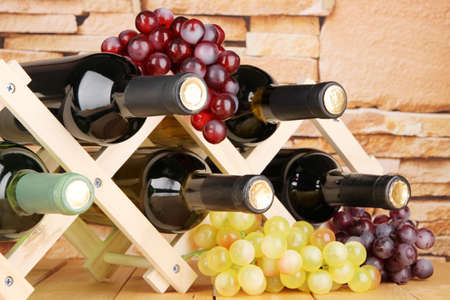 cabarnet: Bottles of wine placed on wooden stand on stone wall background